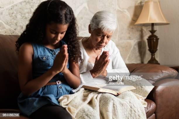 年配の女性と少女はソファの上に座って、祈り