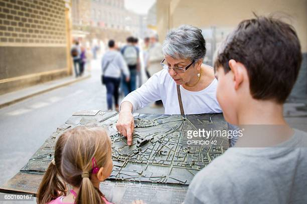 Senior woman and grandchildren pointing at city map, Florence, Italy