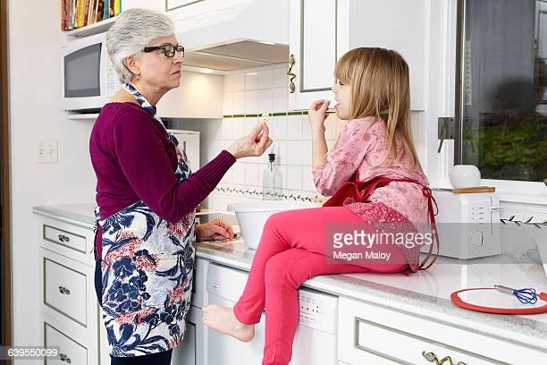 Senior woman and granddaughter eating popcorn at kitchen counter