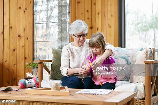 Senior woman and granddaughter knitting together on living room sofa