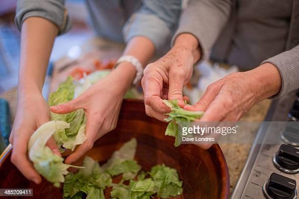 Senior woman and granddaughter preparing lettuce for salad