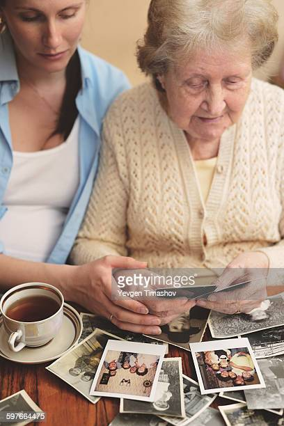 Senior woman and granddaughter sitting at table, looking through old photographs