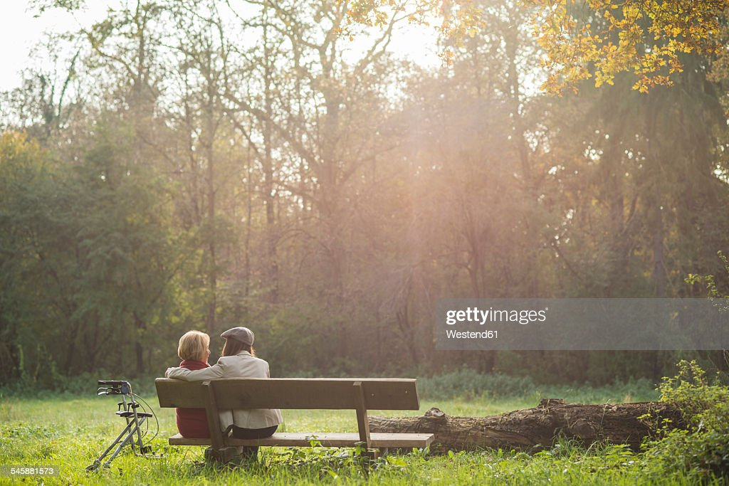 Senior Woman And Granddaughter Sitting On A Park Bench Back View