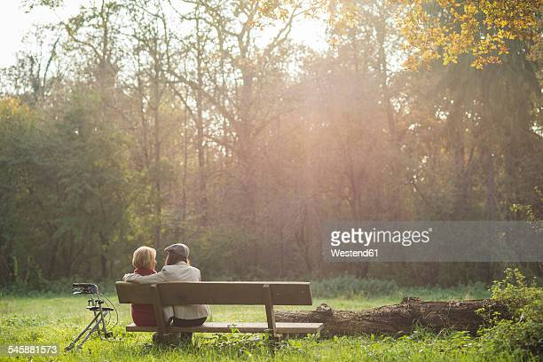 Senior woman and granddaughter sitting on a park bench, back view