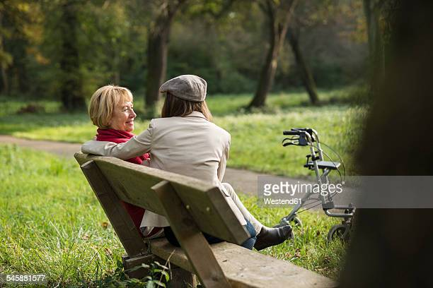 Senior woman and granddaughter sitting on a park bench