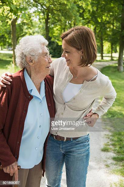 Senior woman and granddaughter standing in park