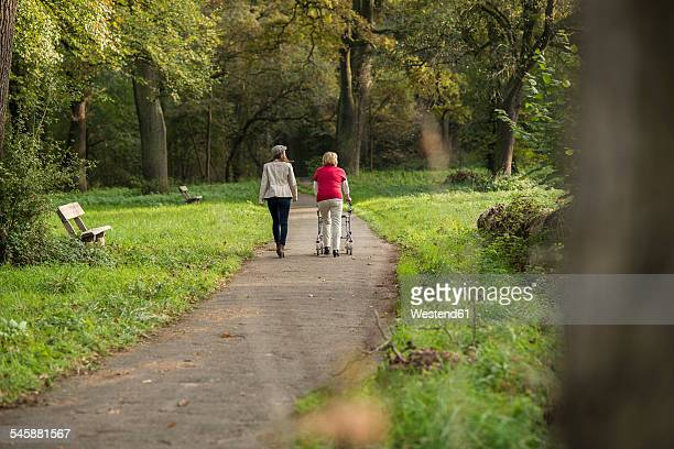 Senior woman and granddaughter walking together in a park, back view