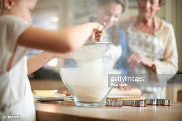 Senior woman and granddaughters sifting flour for Christmas tree cookies