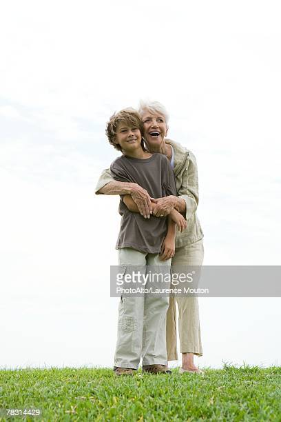 senior woman and grandson standing on grass, woman hugging boy from behind, both smiling and looking out of frame, full length - out of frame stock pictures, royalty-free photos & images
