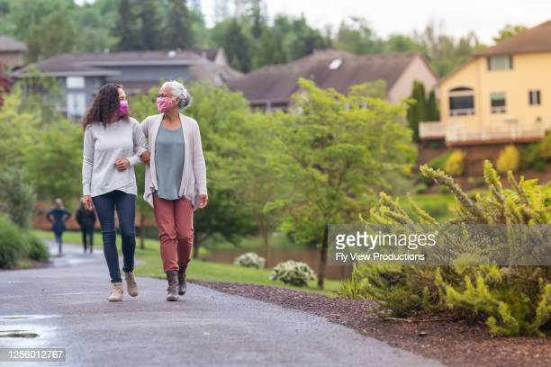 senior woman and her adult daughter enjoying the outdoors together during coronavirus - pacific islanders stock pictures, royalty-free photos & images