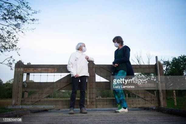 senior woman and her daughter sporting a home made face mask - lucy lambriex stockfoto's en -beelden