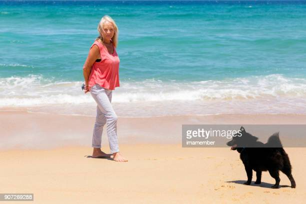 Senior woman and her dog on the beach, background with copy space
