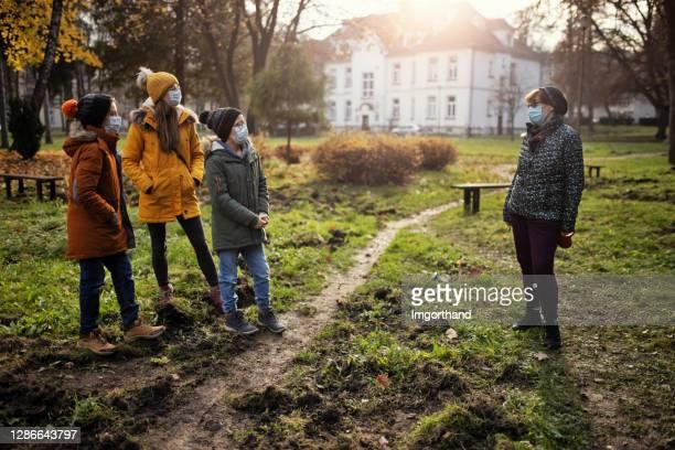 seniorin und ihre enkelkinder treffen sich während der covid-19-pandemie im park - abstand halten infektionsvermeidung stock-fotos und bilder