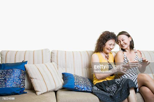 senior woman and her granddaughter looking photographs in a digital camera and smiling - asian granny pics stock photos and pictures