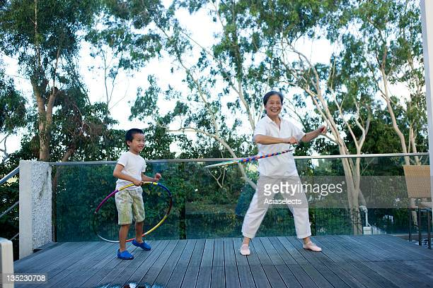 Senior woman and her grandson spinning plastic hoops around their waists