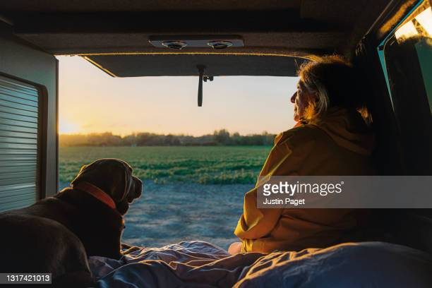 senior woman and her pet dog looking at the view from the back of her campervan - cancer illness stock pictures, royalty-free photos & images