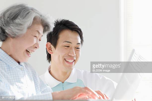 Senior woman and male care worker using laptop PC