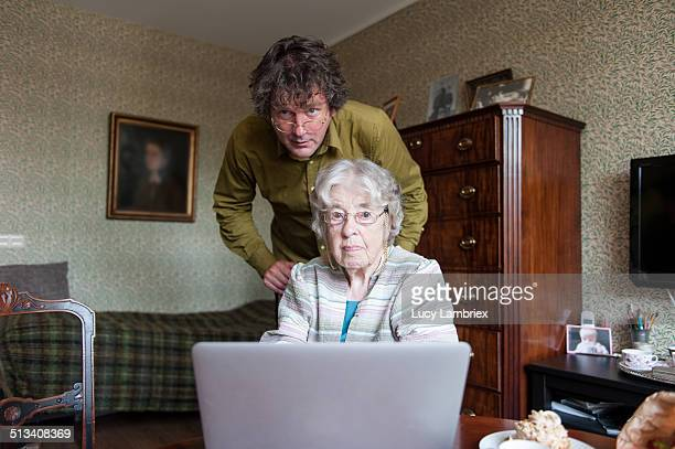 Senior woman and mature man with laptop