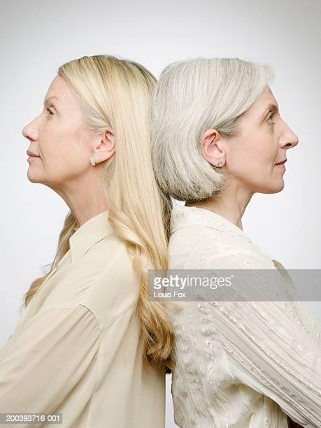 Senior woman and mature woman back to back, side view