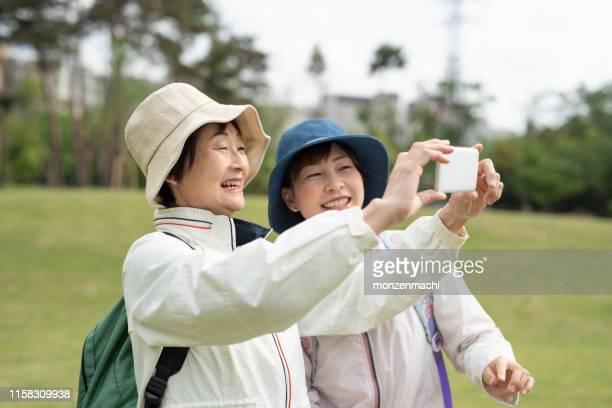 公園で自分撮りをするシニア女性と中大人の女性 - 撮影テーマ ストックフォトと画像