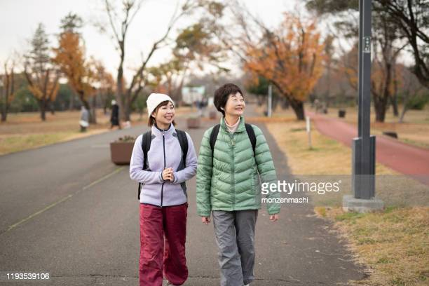 senior woman and mid adult woman walking in autumn park - number of people stock pictures, royalty-free photos & images