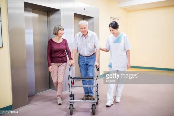 Ältere Frau und Krankenschwester hilft Menschen mit walking frame