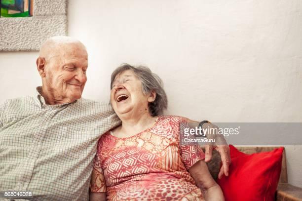 senior vrouw en senior man zittend op de bank - senioren koppel stockfoto's en -beelden