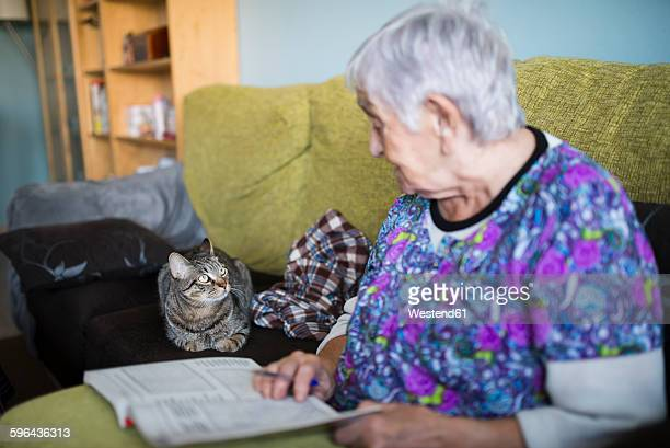 Senior woman and tabby cat on the couch at home looking at each other