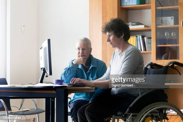 senior woman and woman in a wheelchair sitting at a table, working on computer. - sigrid gombert stock pictures, royalty-free photos & images