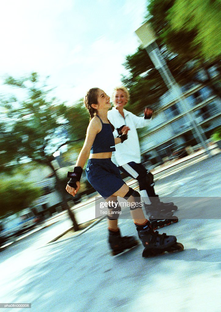 Senior woman and young girl in line skating, blurred. : Stockfoto