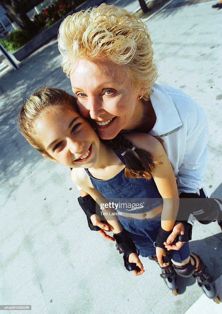 Senior woman and young girl on in line skates, smiling. : Stockfoto