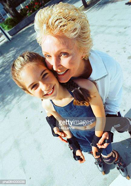 Senior woman and young girl on in line skates, smiling.