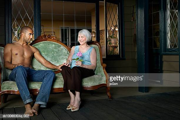 Senior woman and young man sitting on porch holding hands