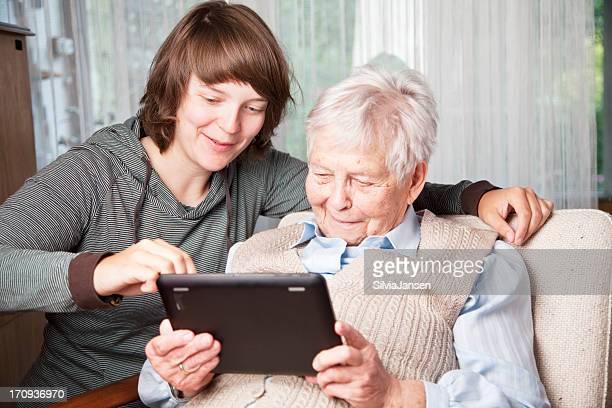 Mulher idosa e jovem usando tablet digital