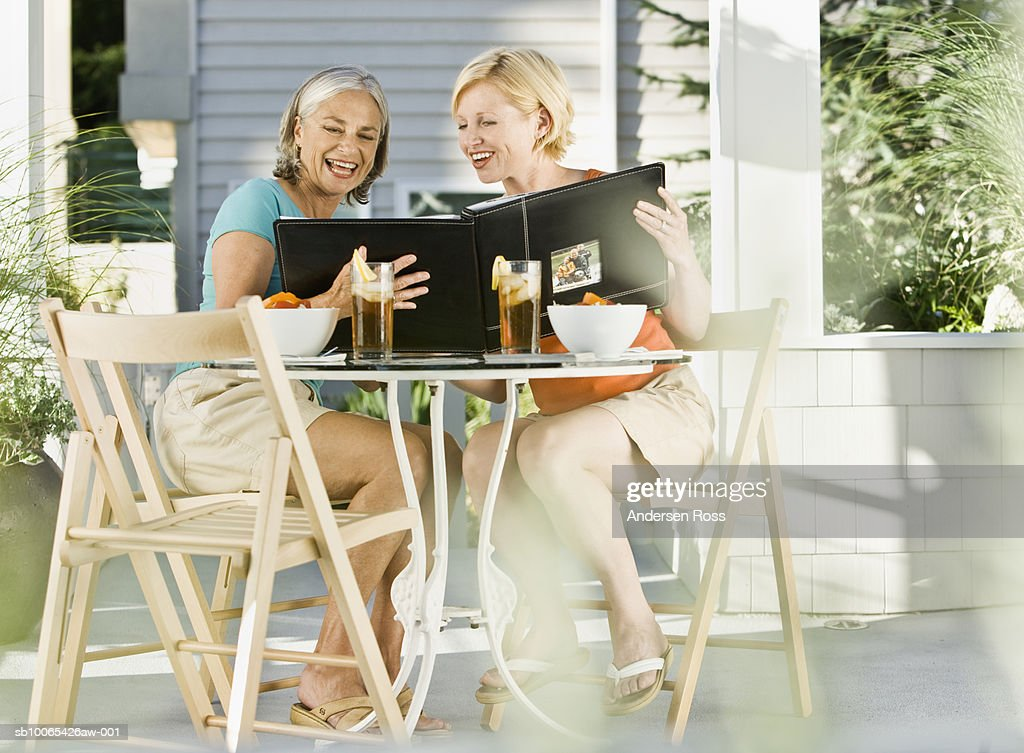 Senior Woman and Young Woman drinking ice tea looking at Photo Album : Foto stock
