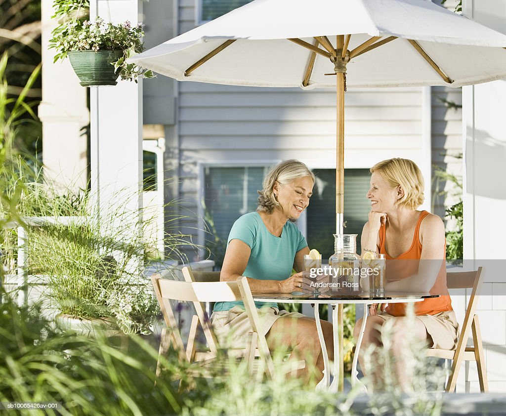 Senior Woman and Young Woman drinking ice tea out on Porch : Foto stock