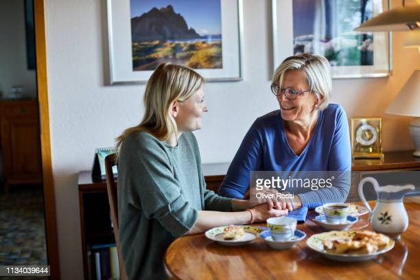 senior woman and young woman sitting at dining table holding hands - visit stock pictures, royalty-free photos & images