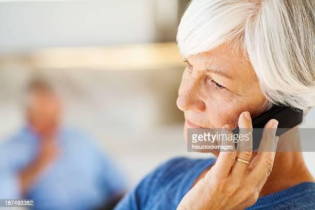 Senior Frau beantworten Smartphone mit Mann im Hintergrund