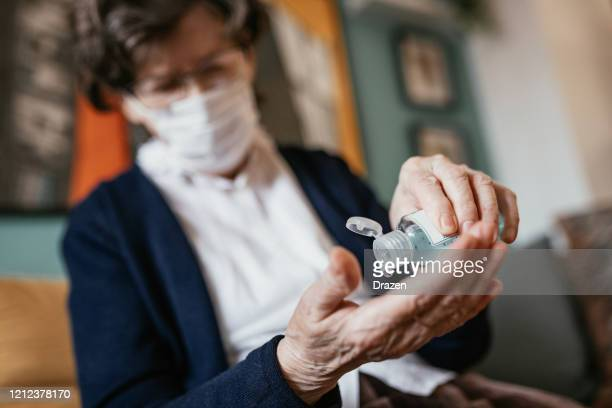 senior woman applying hand sanitizer at home - alcool gel imagens e fotografias de stock