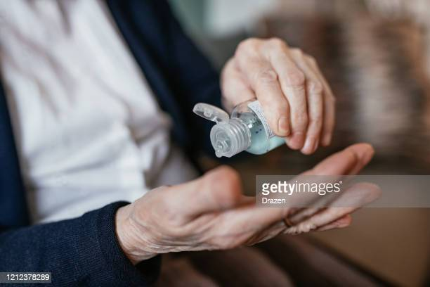 senior woman applying hand sanitizer at home - hand sanitizer stock pictures, royalty-free photos & images
