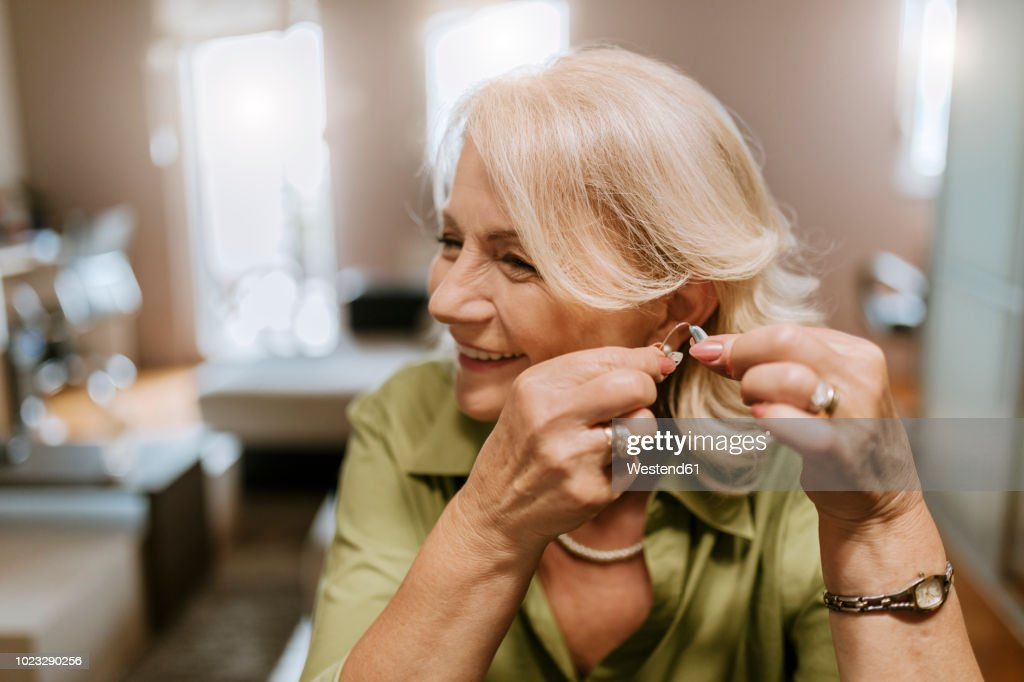 Senior woman applying hearing aid : Stock Photo