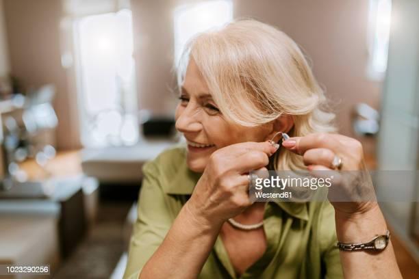 Senior woman applying hearing aid