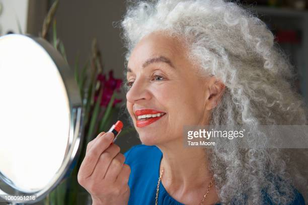 senior woman applying lipstick in mirror - applying stock pictures, royalty-free photos & images