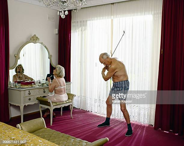 Senior woman applying makeup and senior man swinging golf club