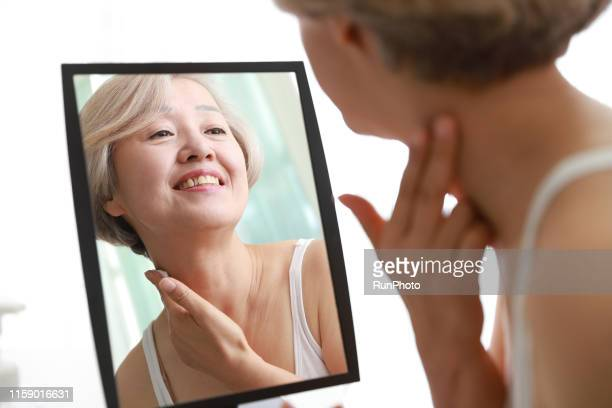 senior woman applying moisturizer on neck - 人の肌 ストックフォトと画像