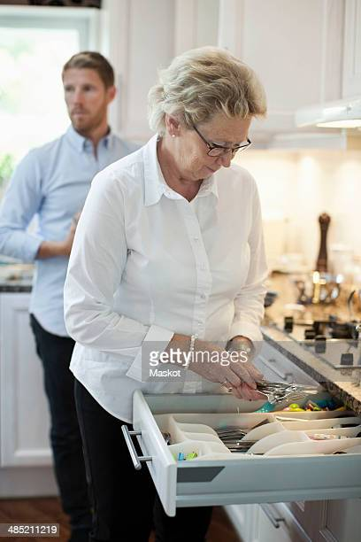 Senior woman arranging cutlery with son standing in background at kitchen