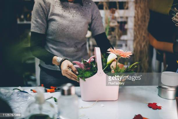 senior woman arranging flower decorations - obscured face stock pictures, royalty-free photos & images