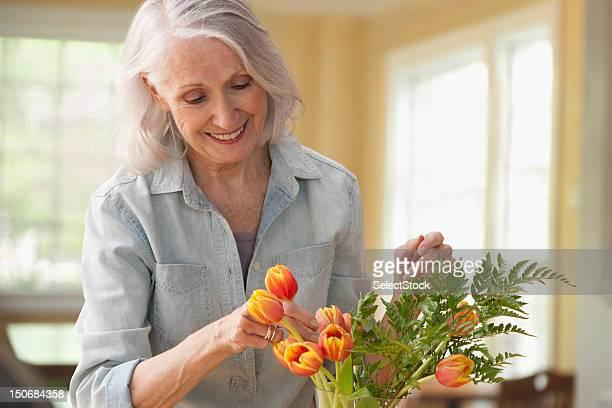 Senior woman arranging flowers