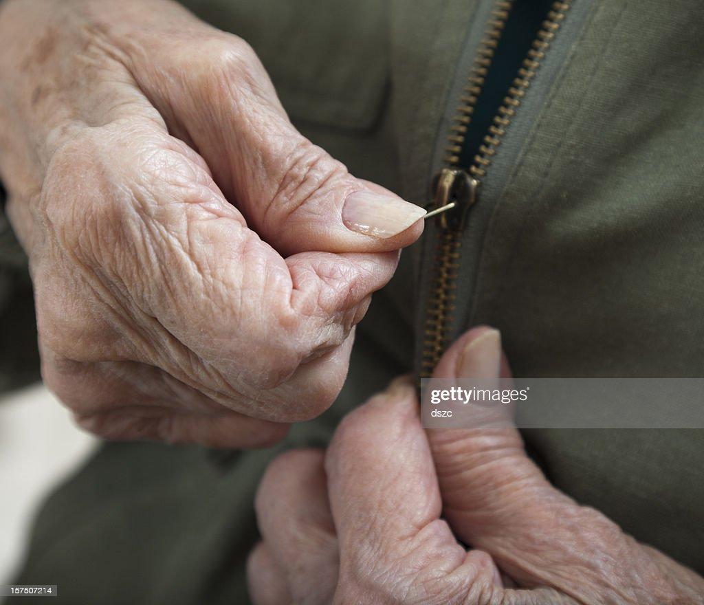 senior woman arthritis hands zipping zipper on jacket : Stock Photo
