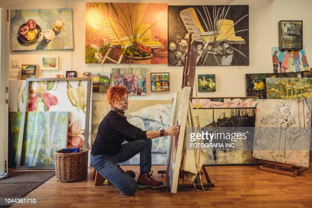 senior woman artist at work - active seniors stock pictures, royalty-free photos & images
